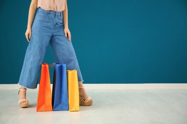 Schöne junge frau mit einkaufstüten gegen farbwand