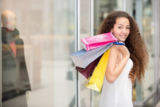 Schöne junge frau mit einkaufstüten im einkaufszentrum