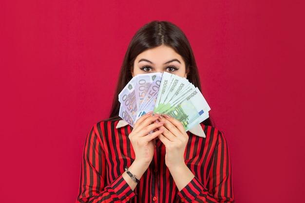 Schöne junge frau mit euro in den händen