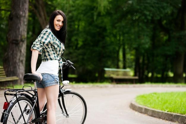 Schöne junge frau mit fahrrad im park