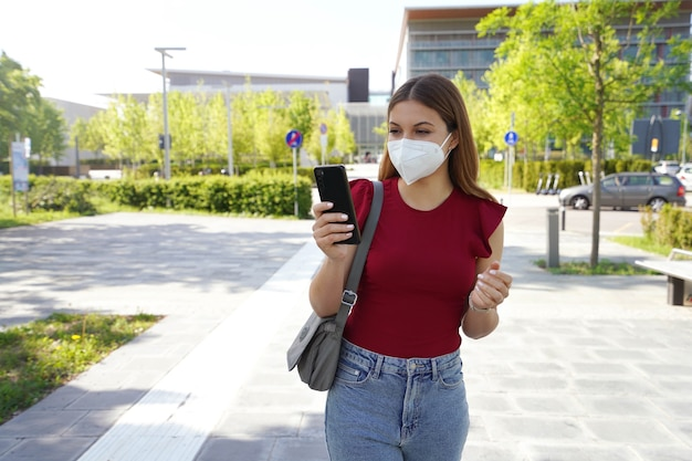 Schöne junge frau mit ffp2-maske mit smartphone-app im freien