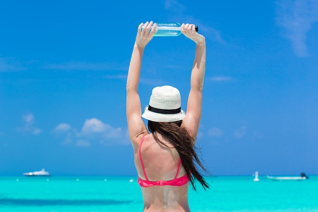 Schöne junge frau mit flasche am strand