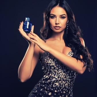 Schöne junge frau mit flasche parfüm auf dunklem raum