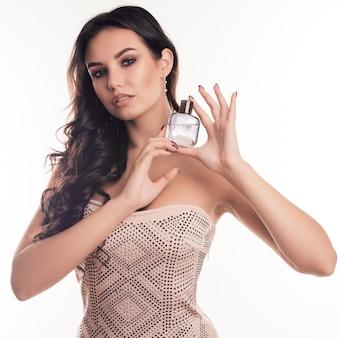 Schöne junge frau mit flasche parfüm