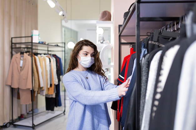 Schöne junge frau mit freundin, die sicheres einkaufen im bekleidungsgeschäft während einer pandemie in masken tut