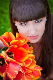 Schöne junge frau mit frühlingstulpen blüht blumenstrauß an der stadtstraße. glückliches mädchen lächelt und hält rote tulpenblumen im freien. frühlingsporträt der hübschen frau im park.