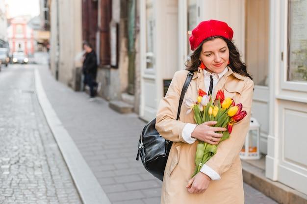 Schöne junge frau mit frühlingstulpenblumenstrauß an der stadtstraße. glückliches mädchen, das draußen geht. frühlingsporträt der hübschen frau in der altstadt