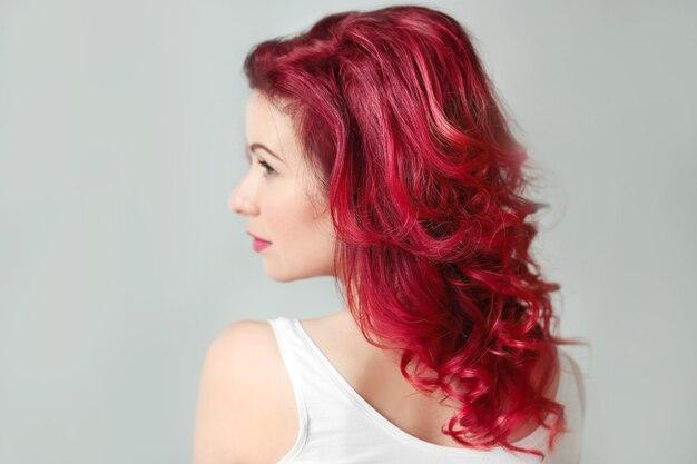 Schöne junge frau mit gefärbtem lockigem haar drinnen