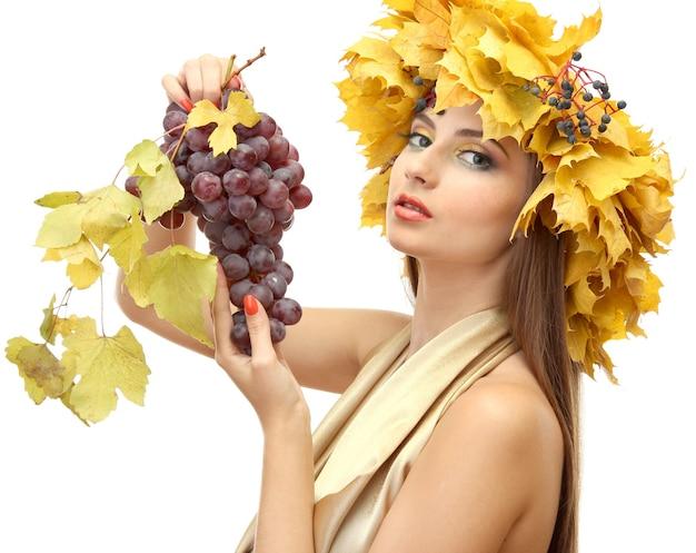 Schöne junge frau mit gelbem herbstkranz und trauben, lokalisiert auf weiß