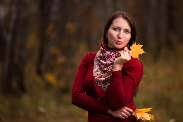 Schöne junge frau mit gelben ahornblättern in den händen