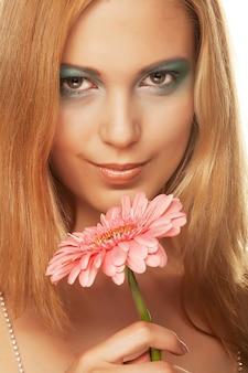 Schöne junge frau mit gerberblume