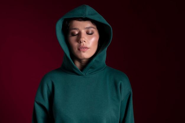 Schöne junge frau mit geschlossenen augen, die einen hoodie trägt