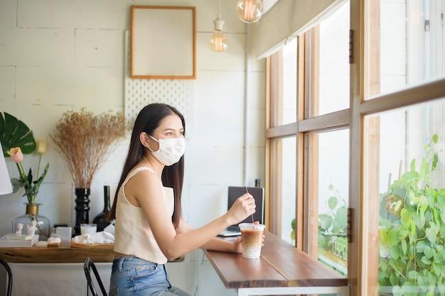 Schöne junge frau mit gesichtsmaske sitzt im coffeeshop