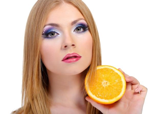 Schöne junge frau mit glamour-make-up und orange, isoliert auf weiß