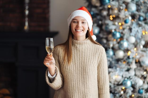 Schöne junge frau mit glas champagner zu hause