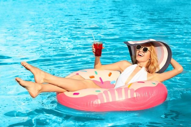 Schöne junge frau mit glascocktail, der auf aufblasbarem donut im pool entspannt