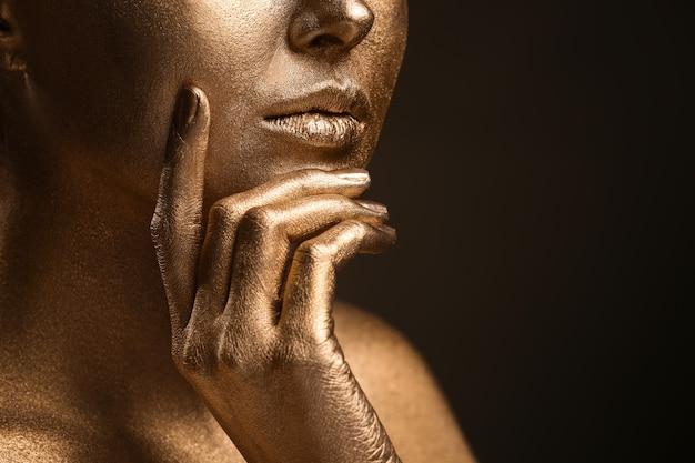 Schöne junge frau mit goldener farbe auf ihrem körper gegen dunklen hintergrund, nahaufnahme