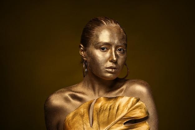 Schöne junge frau mit goldener farbe auf ihrem körper und tropischem blatt gegen dunkle oberfläche