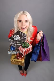 Schöne junge frau mit haufen weihnachtsgeschenke und einkaufstüten