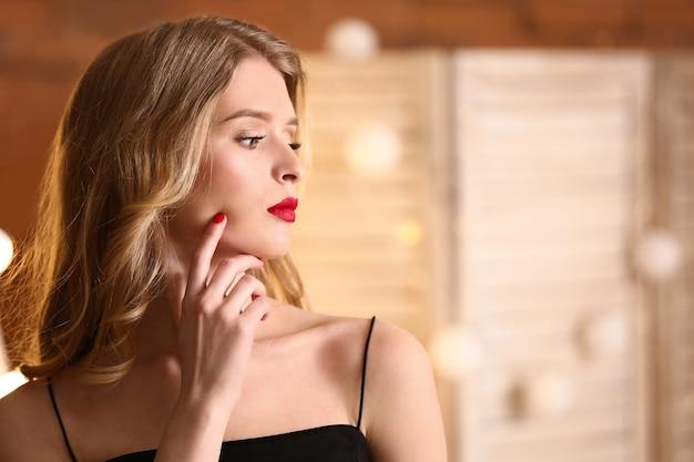Schöne junge frau mit hellem make-up drinnen