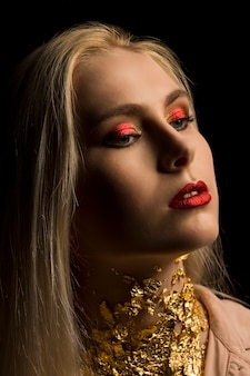 Schöne junge frau mit hellem make-up in roter farbe und goldfolie am hals