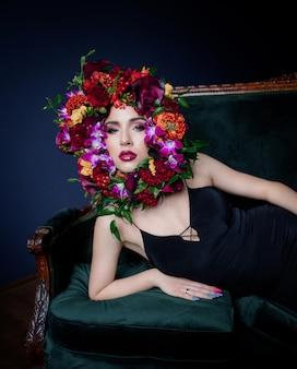 Schöne junge frau mit hellem make-up liegt auf dem grünen sofa, gesicht umgeben von bunten frischen blumen auf dem dunkelblauen hintergrund