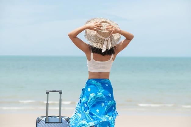 Schöne junge frau mit hut, der mit koffer auf dem wunderbaren meereshintergrund steht, konzept der reisezeit, mit platz für ihren text