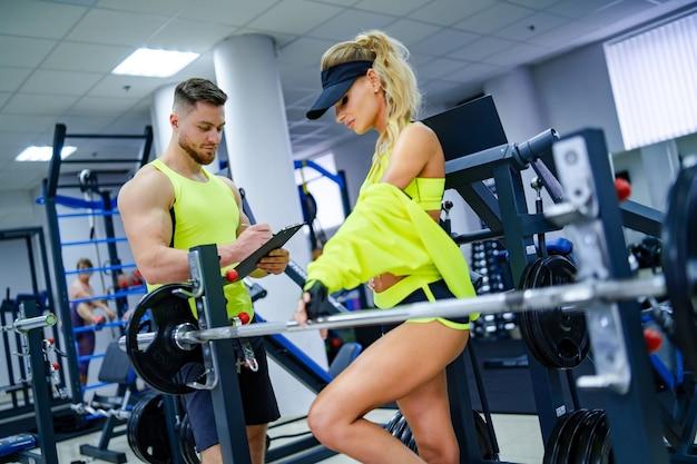 Schöne junge frau mit ihrem persönlichen trainer im fitnessstudio besprechen ihre fortschritte auf einer zwischenablage, die der mann hält. gesunder lebensstil