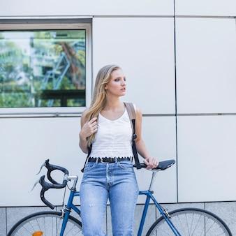Schöne junge frau mit ihrem rucksack, der auf fahrrad sich lehnt
