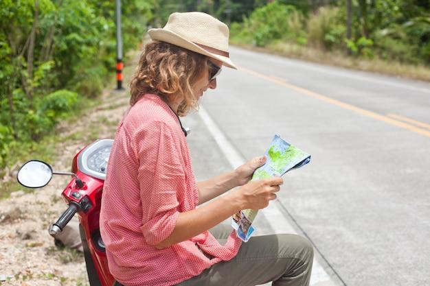 Schöne junge frau mit karte in der hand und einem motorrad auf der straße. reisen, navigation, tourismus