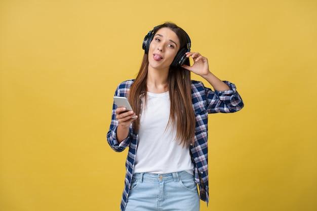 Schöne junge frau mit kopfhörern, die musik hört und auf gelbem hintergrund tanzt.