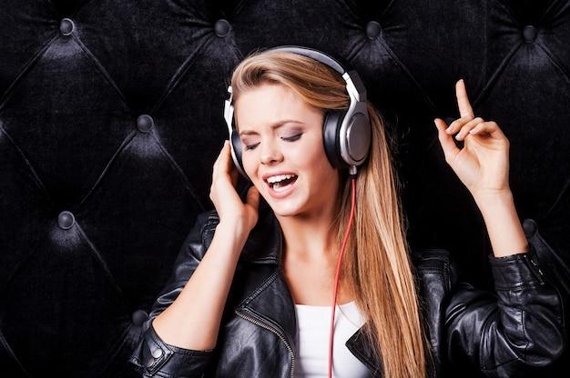 Schöne junge frau mit kopfhörern, die vor schwarzem hintergrund singt