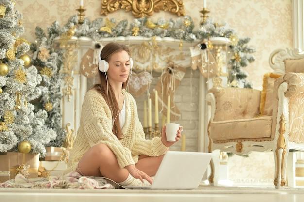 Schöne junge frau mit kopfhörern mit laptop beim sitzen in der nähe von weihnachtsbaum