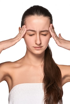 Schöne junge frau mit kopfschmerzen, die ihre schläfen berühren