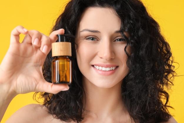 Schöne junge frau mit kosmetischem produkt auf farbhintergrund