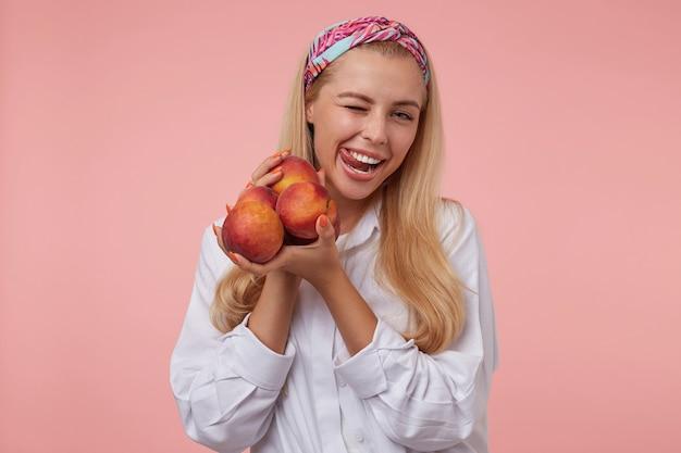 Schöne junge frau mit langen blonden haaren, die spaß haben, zwinkern und zunge mit breitem lächeln herausziehen, freizeitkleidung tragend
