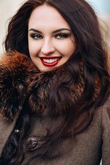 Schöne junge frau mit langen blonden haaren mit natürlichem make-up, das langes kleid der partei, fell, braune körperhaut reine natürliche schönheit trägt, modellkleidungskatalog winterkollektion modestil