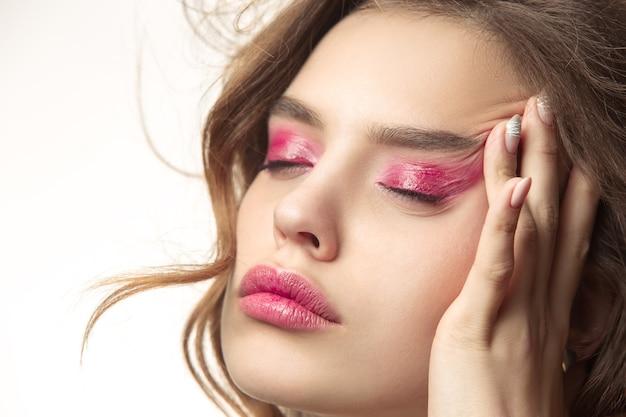 Schöne junge frau mit langen, gewellten, seidigen haaren, natürliches make-up mit der hand in der nähe des kinns, isoliert auf weißer wand. model mit natürlichem make-up.