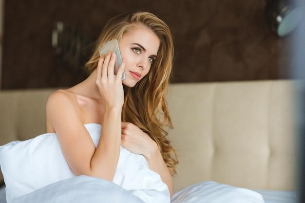 Schöne junge frau mit langen haaren mit smartphone im schlafzimmer