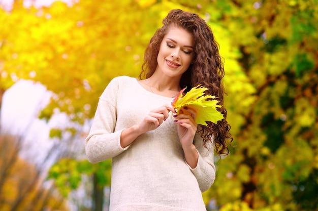 Schöne junge frau mit langen lockigen haaren geht im herbst in den park und sammelt blätter