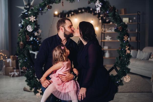 Schöne junge frau mit langen schwarzen gewellten haaren im kleid, attraktiver starker mann mit kurzen dunklen haaren im hemd und jeans verbringen weihnachtszeit zusammen mit einem kleinen mädchen