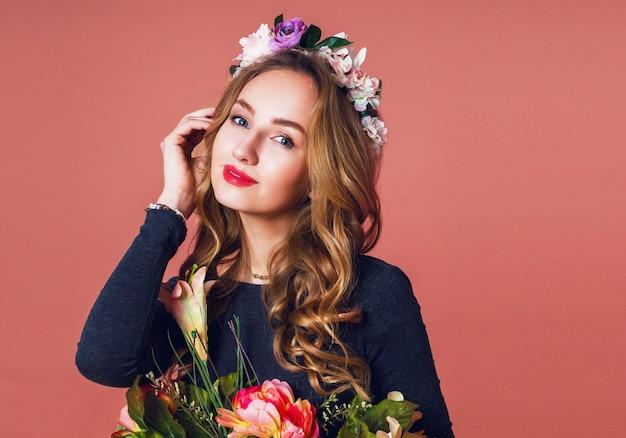 Schöne junge frau mit langen welligen blonden haaren im kranz der frühlingsblumen, die mit blumenstrauß über rosa hintergrund aufwerfen.
