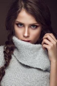 Schöne junge frau mit leichtem make-up in der warmen strickjacke und im langen geraden haar