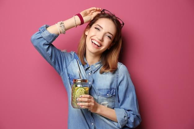 Schöne junge frau mit limonade auf farbhintergrund