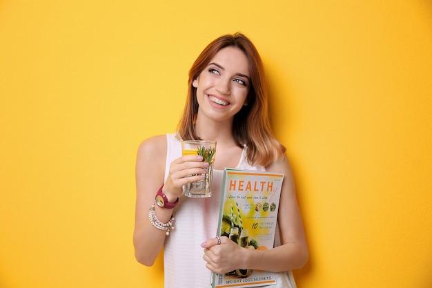 Schöne junge frau mit limonade und zeitschrift auf farbe