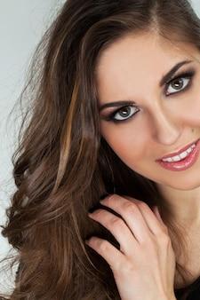 Schöne junge frau mit locken und make-up