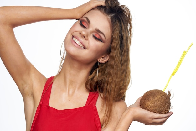 Schöne junge frau mit lockigem haar in einem badeanzug trinkt einen cocktail aus kokosnuss, tropen