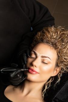 Schöne junge frau mit lockigem haar mit permanentem lippen-make-up im schönheitssalon