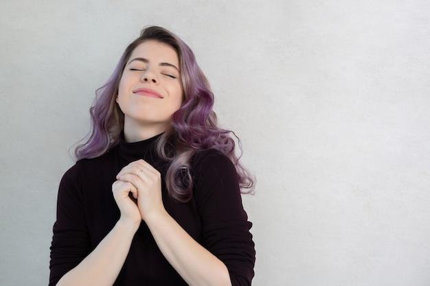 Schöne junge frau mit lockigen lila haaren träumend, posiert auf grauem hintergrund. platz für text