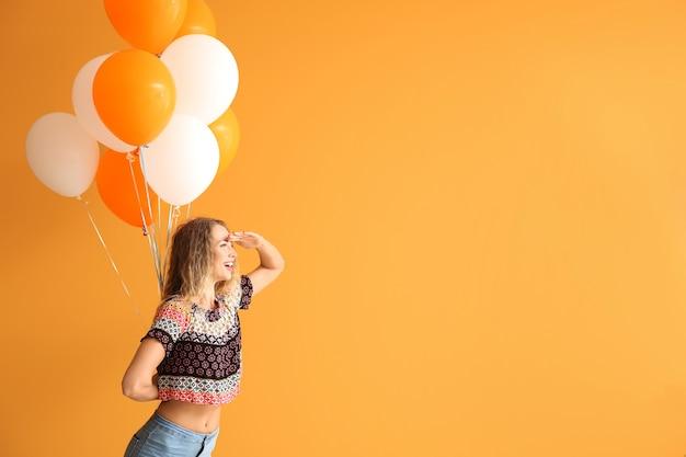 Schöne junge frau mit luftballons